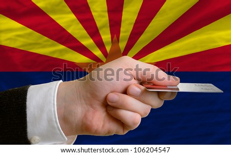 man stretching out credit card to buy goods in front of complete wavy national flag of american state of arizona
