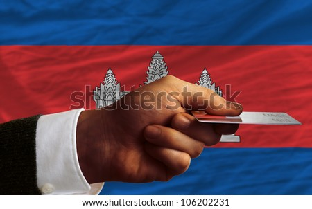man stretching out credit card to buy goods in front of complete wavy national flag of cambodia