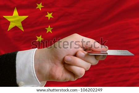 man stretching out credit card to buy goods in front of complete wavy national flag of china