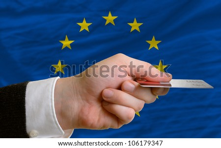 man stretching out credit card to buy goods in front of complete wavy national flag of europe