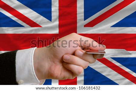 man stretching out credit card to buy goods in front of complete wavy national flag of great britain
