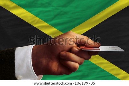 man stretching out credit card to buy goods in front of complete wavy national flag of jamaica