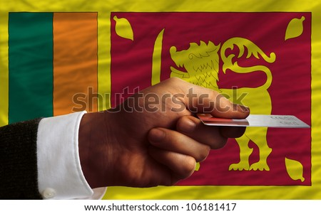man stretching out credit card to buy goods in front of complete wavy national flag of sri lanka