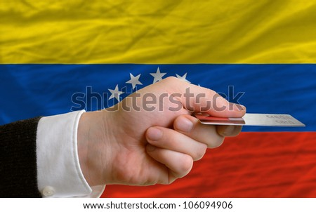 man stretching out credit card to buy goods in front of complete wavy national flag of venezuela - stock photo