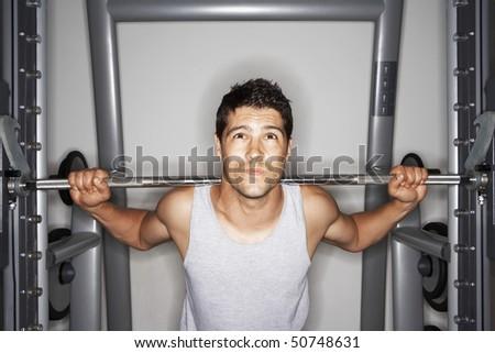 Man struggling to lift Weights on weight machine