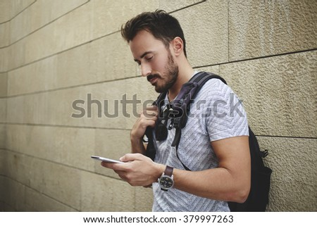 Man student reading information in internet via cell telephone before start lectures in University, bearded hipster guy with rucksack watching video on mobile phone while waiting friends outdoors