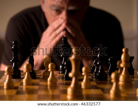 Man studying chess board, selective focus