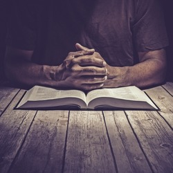 Man studying the Holy Bible on a wooden table.