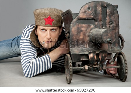 Man stylized like a Soviet soldier in World War II, sitting with old machine-gun  and smoking. Studio shot