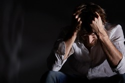 Man suffering emotional pain, holding head in his hands