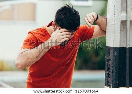 Man suffering from dizziness with difficulty standing up while leaning on wall #1157001664