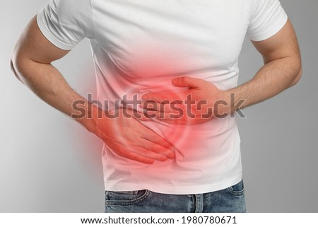 Man suffering from pain in lower right abdomen on light grey background, closeup. Acute appendicitis Foto stock ©