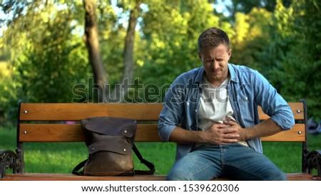 Man suffering stomach ache sitting bench, gastritis problem, food poisoning Zdjęcia stock ©