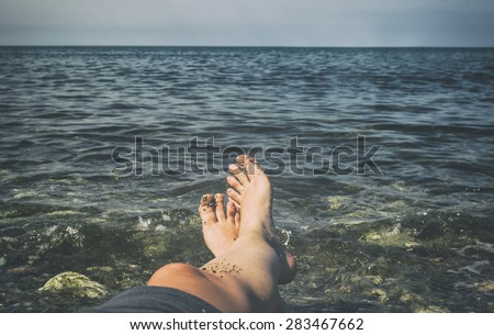 Man sunbathing on beach. Legs. Vintage effect.