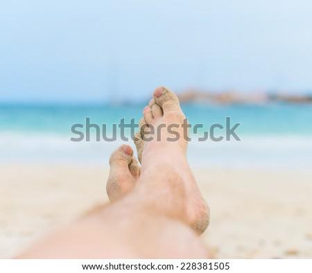 Man sunbathing on the beach. Legs.