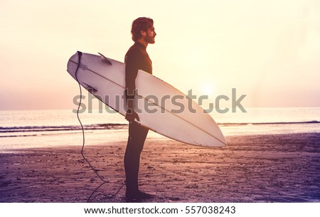 Stock Photo Man surfer carrying his surfboard at sunrise - Hipster male in wetsuit waiting for the high waves on beach - Extreme sport concept - Focus on male silhouette - Matte filter with soft blue vignette
