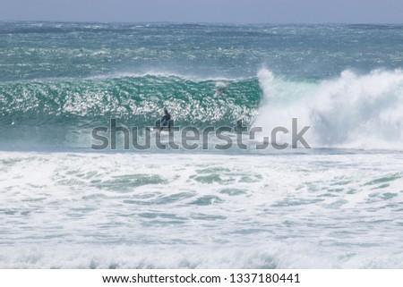 man surfer catching big wave tropical emerald green ocean from Kirra beach Gold Coast Queensland Australia coolangatta