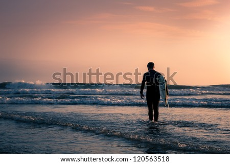 Man surfer in black diving suit with white surfboard on the beach at sunset. Focused on foreground.