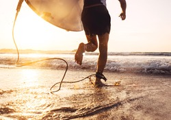 Man surfer run in ocean with surfboard. Active vacation, health lifestyle and sport concept image