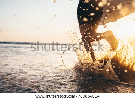 Stock Photo Man surfer run in ocean with surfboard. Closeup image water splashes and legs, sunset light