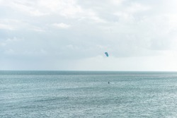 Man surfing, kitesurfing with kite on board in Florida at ocean, sea in distance far away in Bahia Honda Key Keys