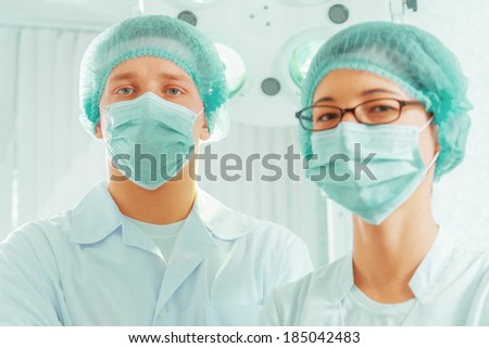 Man surgeon and nurse in a mask and a cap in an operating room