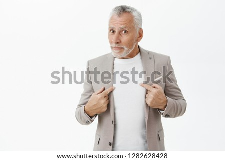 Man surprised and questioned being picked by boss standing unsure over grey wall in elegant formal suit pointing at himself and gazing confused at camera asking uncertain if people talking about him #1282628428