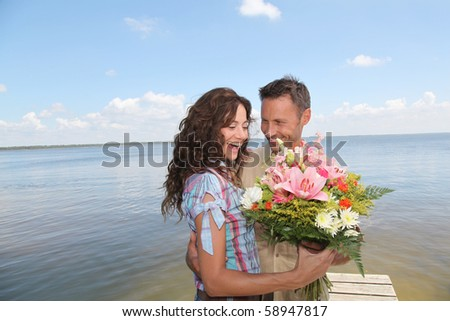 Man surprising woman with bunch of flowers