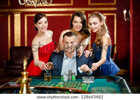 Man surrounded by women plays roulette at the casino