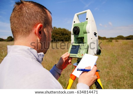 Man surveyor at work and using of total station. Survey Instrument geodetic device, total station set and surveyor worker making measurement in the field. Total station outdoor at construction site.