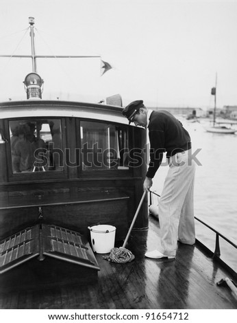 Man swabbing deck of boat