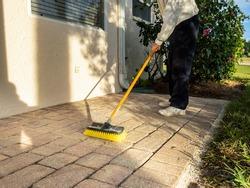 Man sweeping brick paver stone porch with push broom.
