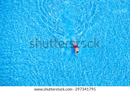 Man swim in the pool at the hotel. View from above.