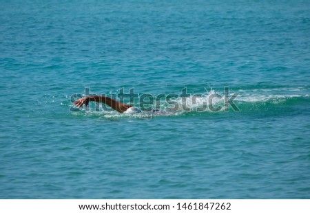 Man swimmer shows freestyle stroke swimming technique in the turquoise blue sea ocean #1461847262