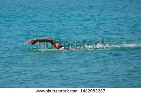 Man swimmer shows freestyle stroke swimming technique in the turquoise blue sea ocean #1462083287