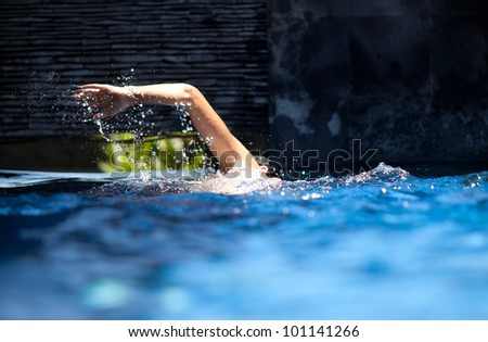 Man swimming crawl in private pool with splash arm
