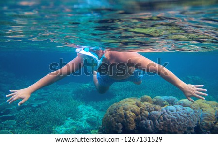 Man swimming in blue water undersea. Snorkel in coral reef of tropical sea. Young man in full-face snorkeling mask. Underwater photo of coral reef landscape. Summer vacation on tropic island seashore