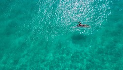 Man swimming in the sea. Aerial view. Top view.amazing nature background.The color of the water and beautifully bright.