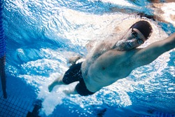 Man swimming the front crawl in a pool. Underwater shot of professional swimmer practising for race in swimming pool.