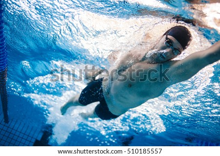 Man swimming the front crawl in a pool. Underwater shot of professional swimmer practising for race in swimming pool. #510185557