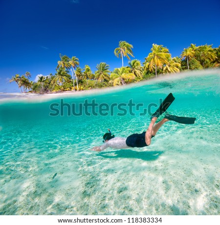 Man swimming underwater in a tropical lagoon