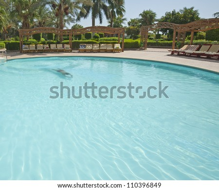 Man swimming underwater in the pool of a tropical hotel resort