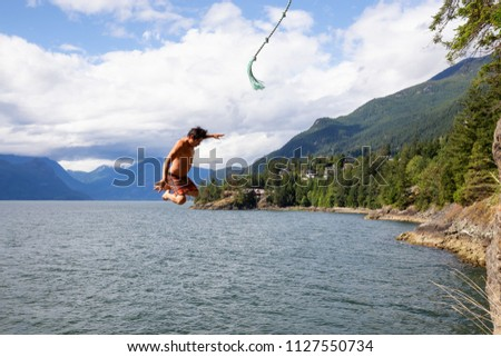 Man swinging from a cliff into the ocean.  Taken Lions Bay, North of Vancouver, BC, Canada Stock photo ©