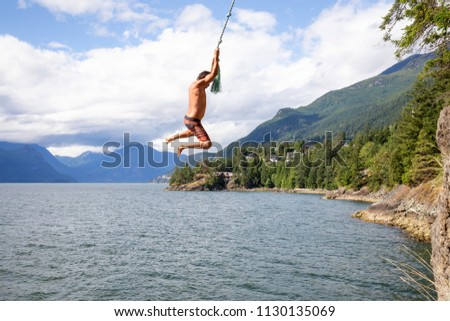 Man swinging from a cliff into the ocean.  Taken Lions Bay, North of Vancouver, BC, Canada #1130135069