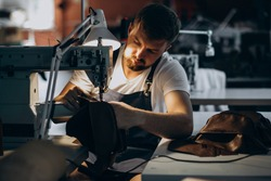 Man tailor working with leather fabric