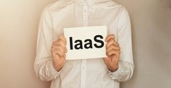 man take a paper with text IaaS on the shirt with office background