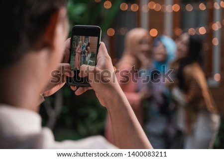 man take photo of three women while relaxing standing on the house yard with house background