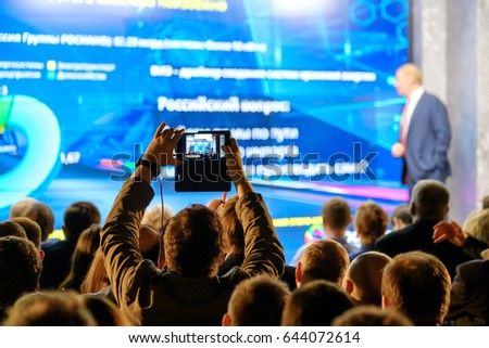 Man takes a picture of the presentation at the conference hall using smartphone #644072614