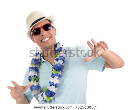 Man takes advantage of the carnival revelry and celebrates. Wearing sunglasses, flower necklace and hat. Young latin american man wearing blue shirt. Isolated on white background.