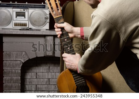 Man takes guitar. The decision to choose acoustic guitar instead of listening to the recording